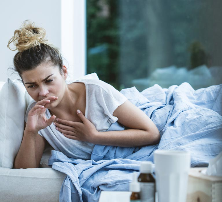 Woman Propping Herself Up In Bed Looking Sick